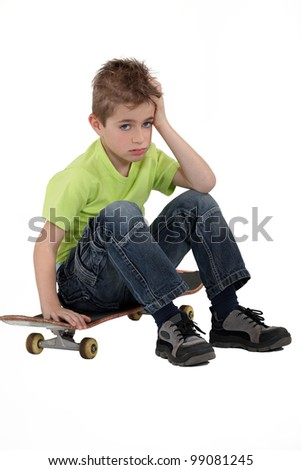 Little boy sat on skateboard - stock photo