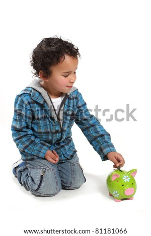 Little boy saving his money by putting it into a piggy bank - stock photo