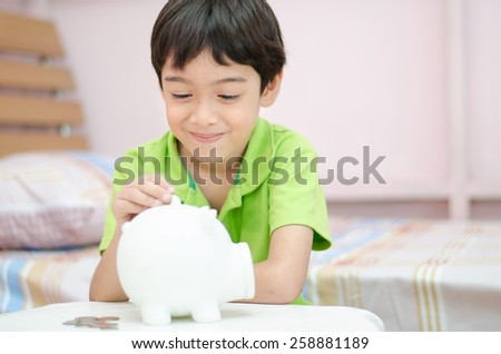 Little boy saving money in piggy bank  - stock photo