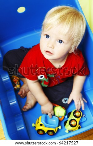 Little boy seating in blue box and playing with toys - stock photo