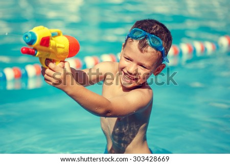 Little boy shooting with water gun in the pool, vintage style - stock photo