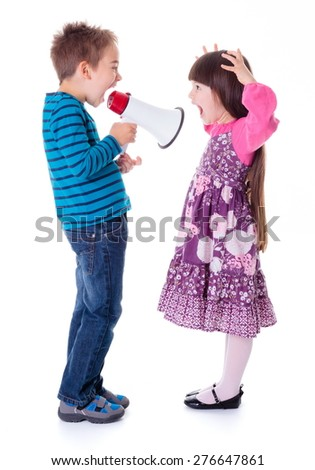 Little boy shouting at girl with megaphone - stock photo