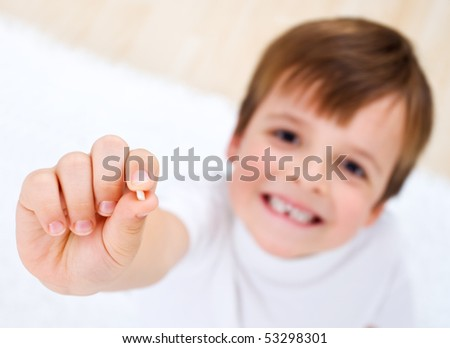 Little boy showing his first lost milk-tooth in his hand - closeup - stock photo