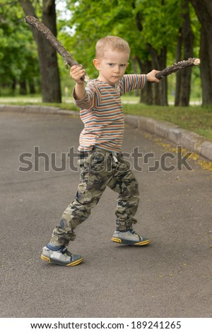 Little boy showing off his stick fighting skills posing with both sticks raised in the air and a determined expression in the middle of a country road - stock photo