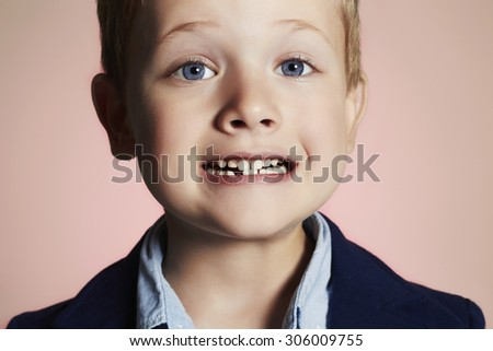little boy showing that he lost first milk tooth.child with missing front tooth - stock photo