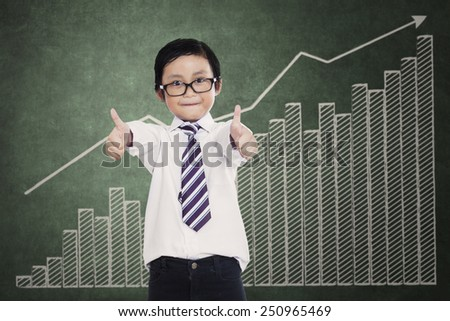 Little boy showing thumbs up with growth graph at classroom - stock photo