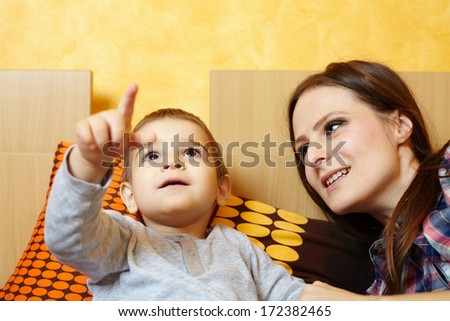 Little boy showing to his mother something on the ceiling - stock photo