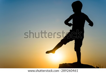 Little boy silhouetted on a wall or rock kicking the fiery orange orb of the setting sun with his foot, with copyspace