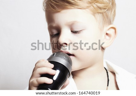 little boy singing in microphone.child in karaoke.music - stock photo