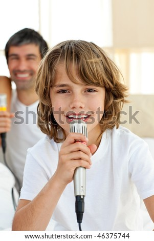 Little boy singing with a microphone sitting on bed - stock photo