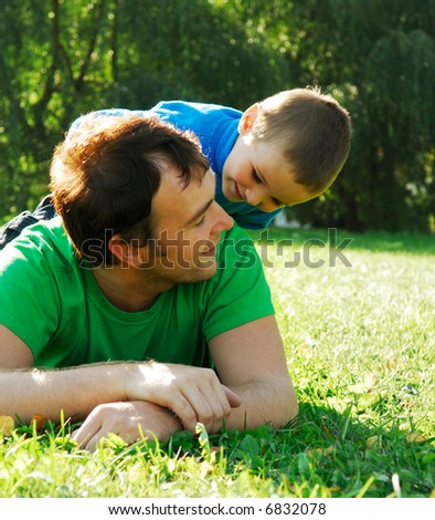 Little boy sit on the father's back and playing - stock photo