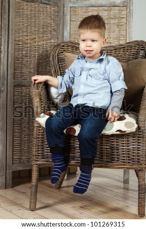 little boy sits in a armchair