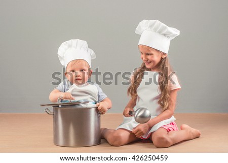 Little boy sits in a large saucepan. Girl is holding a ladle. They are in the studio on a gray background in the hat and chef apron.