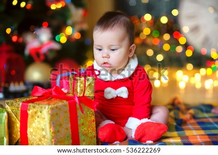 little boy, sits on a floor near gifts. With curiosity considers everything around, on a background a set of bright fires, soft focus.