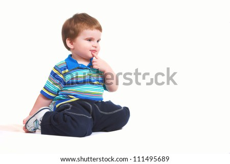 little boy sits on a white background and gestures