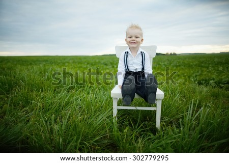 little boy sits on chair in the field