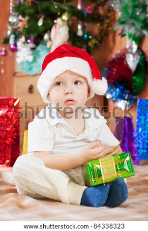 Little boy sits with  Christmas gift at home