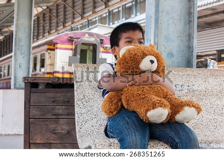 Little boy sitting alone and hand hold bear at the train station - stock photo
