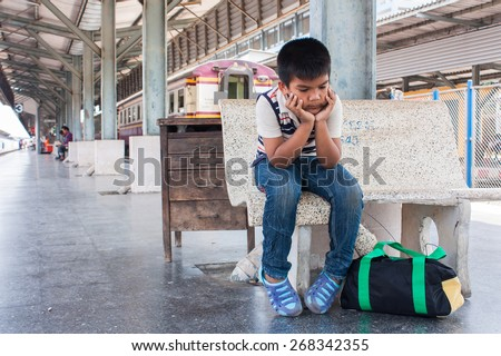 Little boy sitting alone at the train station - stock photo