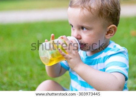Little boy sitting and drinking his beverage at the end of the funny hot summer day full of play - stock photo