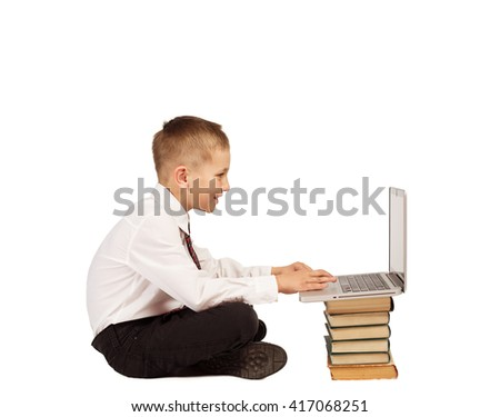 Little Boy sitting and typing on laptop computer and books. Home school, technology education. White background isolated - stock photo
