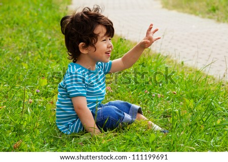 little boy sitting and waving in the park - stock photo