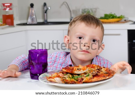 Little boy sitting at a table in the kitchen eating a big plate of homemade Italian pizza with a delicious golden crust