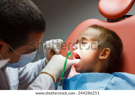 Little boy sitting at dentist for examination - stock photo