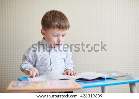 little boy sitting at the desk and reading a book