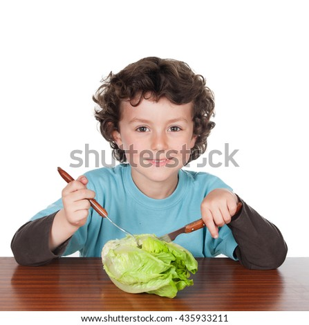 Little boy sitting at the wooden table eating a lettuce isolated on white - stock photo