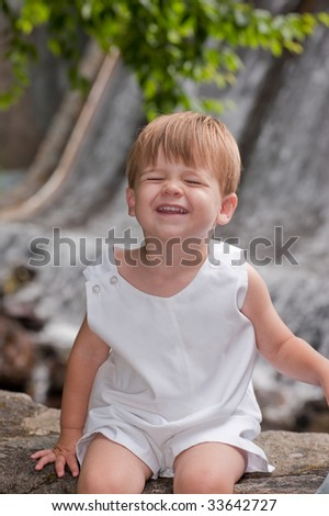little boy sitting by a waterfall grinning at camera with eyes closed - stock photo