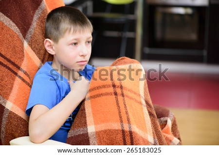 Little boy sitting covered with a blanket at home - stock photo