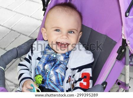 little boy sitting in a stroller - stock photo