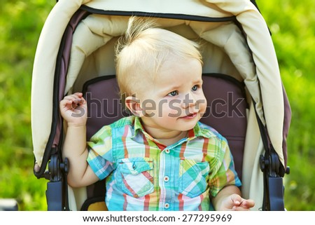 little boy sitting in a stroller. baby for a walk in a pram. summer outdoors - stock photo