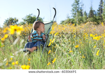 Little boy sitting in a stroller concerned looking for his mom - stock photo