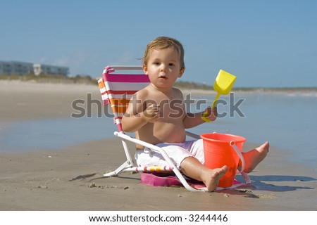 Little boy sitting in beach chair, playing with beach toys