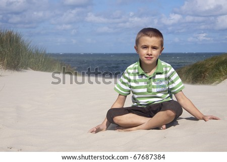 Little boy sitting in sand - stock photo