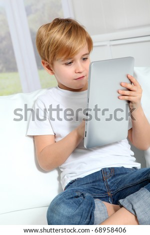 Little boy sitting in sofa with electronic tablet - stock photo