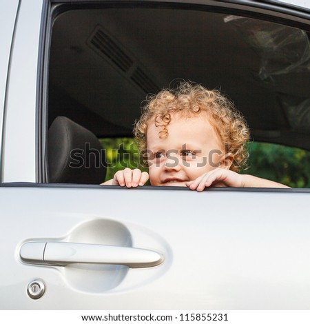 little boy sitting in the car - stock photo