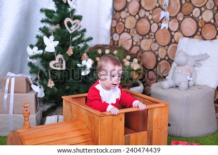Little boy sitting in toy wooden steam locomotive in Christmas interior. Infant son  having fun with Christmas presents in New Year interior. Merry Christmas! - stock photo