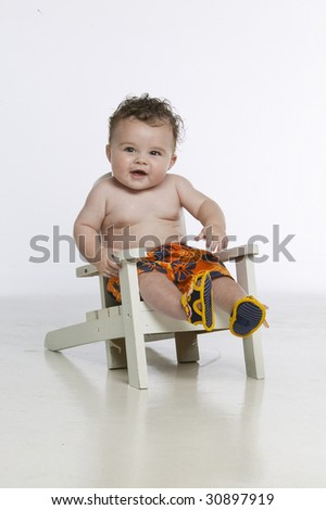 Little boy sitting in white chair - stock photo