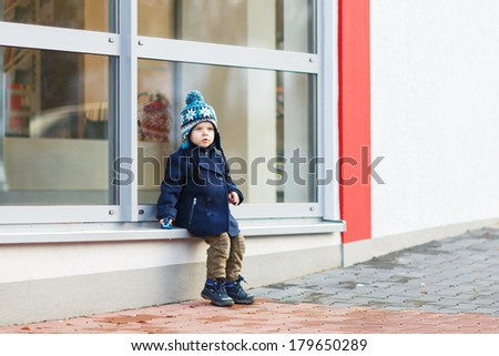 Little boy sitting infront of big window in the city, outdoors, winter.