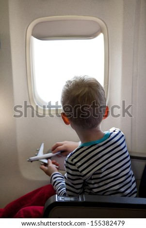 little boy sitting inside the plane and playing with his toy plane - stock photo