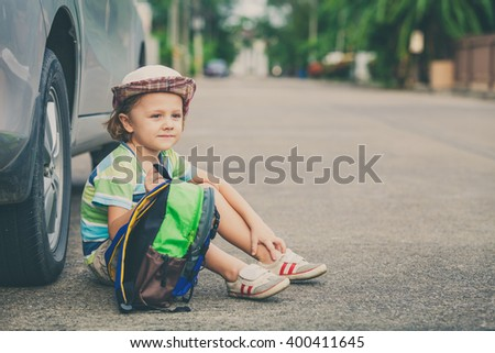 Little boy sitting near the car at the day time. Concept of happy life. - stock photo