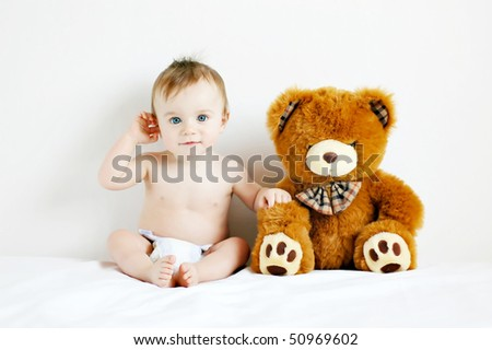 Little boy sitting next to a teddy bear