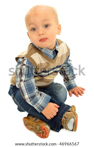 Little boy sitting on a floor against white background