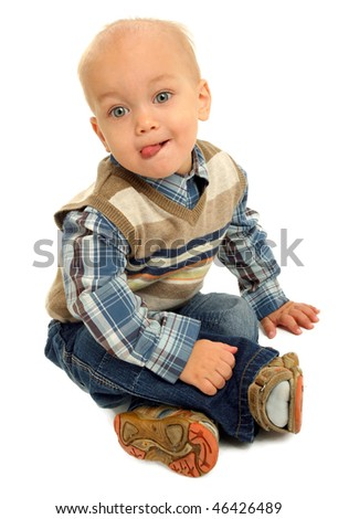Little boy sitting on a floor showing tongue  against white background