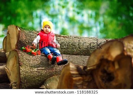little boy sitting on a log - stock photo