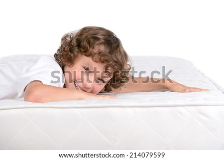 Little boy sitting on a lot of mattresses, isolated on white background - stock photo