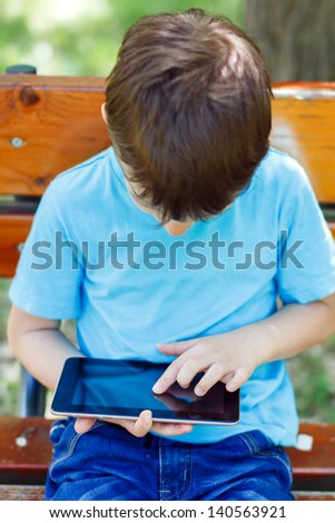 Little boy sitting on bench with tablet, park - stock photo